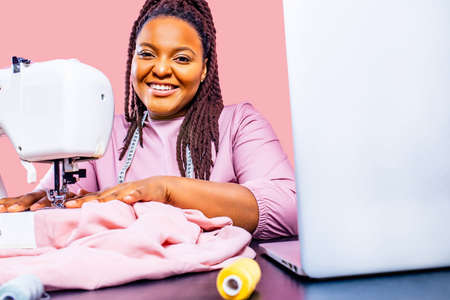 african tailor with afro dreadlocks pigtails sews clothes on sewing machine at tailor office pink wall background