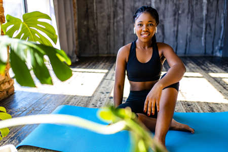 mixed race healthy woman in black sporty suit during her fitness workout at home against the background of panoramic windows sunlight Imagens