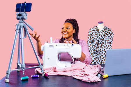 blogger woman demonstrates sewing equipment blog about sewing in studio on pink wall background