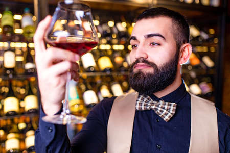 arabian man sommelier appreciating drink in lux hotel Archivio Fotografico