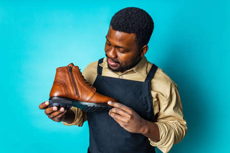 latin hispanic man in black apron showing brown leather shoes in blue studio background Archivio Fotografico