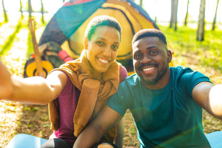 afro latin couple in tent taking selfie using modern smartphone