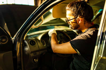 latin hispanic auto mechanic in uniform is examining a car while working in auto service Archivio Fotografico