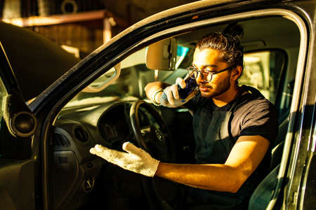 indian mechanic man talking with a customer by phone while sitting in broken car