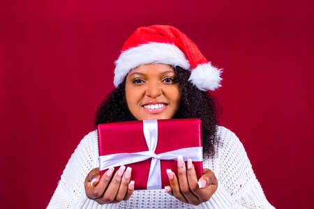 joyful pretty woman in red santa claus hat laughing isolated on red background she is happy and excited full of fun holding gift box Archivio Fotografico