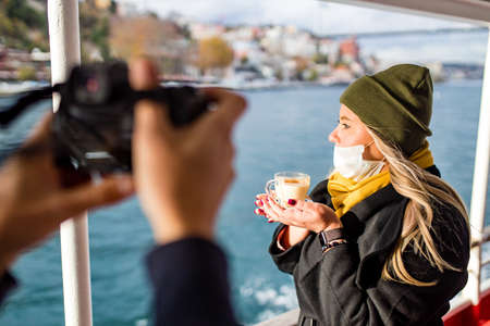 woman drinking hot masala tea in the front, bosphorus bay in the background posing to photographer with camera