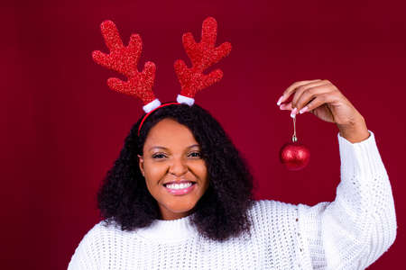 Joyful brazil charming woman in toy deer horns holding red ball gift box while at cozy room