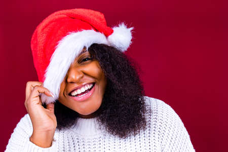 joyful pretty woman in red santa claus hat laughing isolated on red background she is happy and excited full of fun Archivio Fotografico