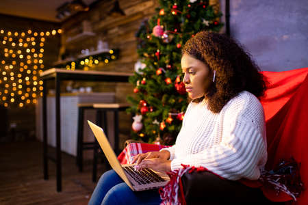 afro woman shopping online on laptop in cozy christmas interior.Preparing to xmas, bying on winter sales Archivio Fotografico