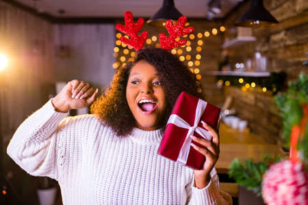 brazil brunette hair woman hold red gift box near fir-tree at her apartment she is wear white sweater and red deer horns
