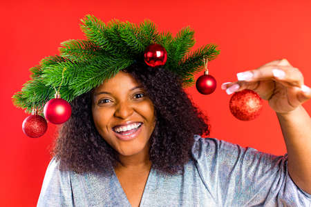 mixed race woman wear crown preparing for Christmas in red studio Archivio Fotografico