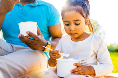 Beautiful little girl and her dad are eating an ice cream in summer sunny park celebrating fathers day Archivio Fotografico
