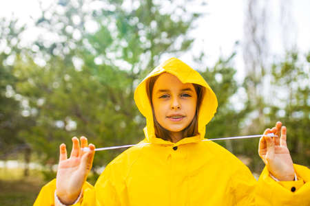 smiling teenage girl wearing raincoat outdoors in rainy day Archivio Fotografico