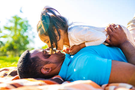 latin hispanic man with cute baby celebrating fathers day at picnic in sunny park