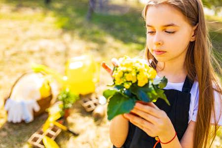 teenager girl in black apron gardening in the backyard garden