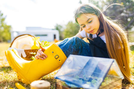beautiful schoolgirl teenager spending time outdoors in garden wear yellow rubber shoes boots looking into a small glasshouse Archivio Fotografico