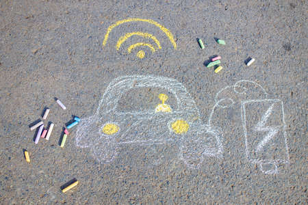 Little girl with creative craft hobby drawing electro on the asphalt with chalk car environment, eco friendly, save energy in park at summer day