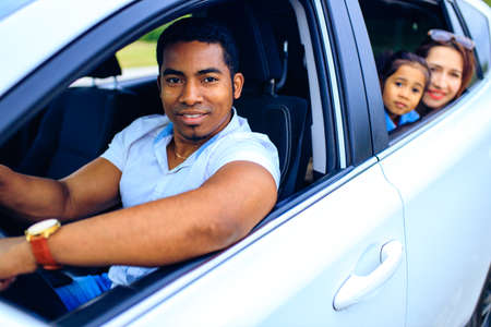 latin hispanic man and beautiful woman with cute daughter ready for trip on car