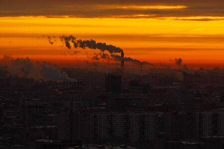 Sunrise over the city. Aerial view of Moscow, silhouettes of buildings in downtown with colorful lighting sunrise sky and soft clouds. Factories pipe, of which there are smoke