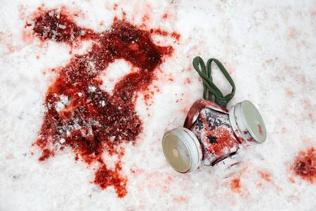 Personal protective equipment gas mask lies in the snow in a puddle of blood