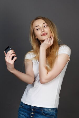young pretty blonde women taking selfie on cell phone in studio photo