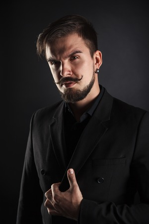 forceful: handsome brutal guy with beard on dark background in studio