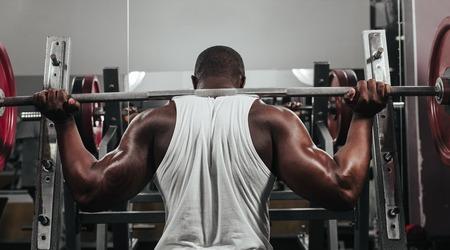 levantar peso: Haciendo entrenamiento con pesas en el gimnasio de musculación africana Foto de archivo