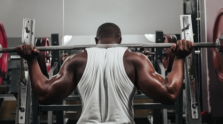 lifting: Weight training African doing bodybuilding in gym Stock Photo