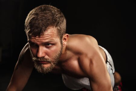 muscle guy: Athletic bearded boxer with gloves doing push ups