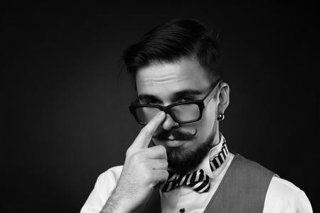 knappe man met baard en snor in pak op donkere achtergrond in de studio