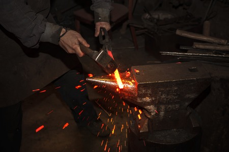 A blacksmith forging hot iron on the anvil Stock Photo