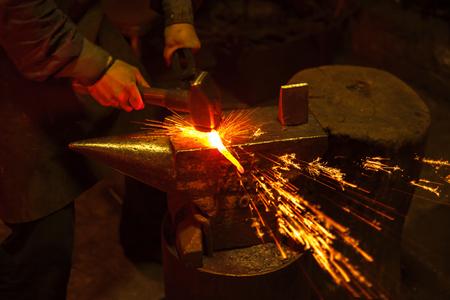 A blacksmith forging hot iron on the anvil Archivio Fotografico