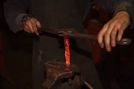 clinch: Blacksmith working with vise rotating metal tool