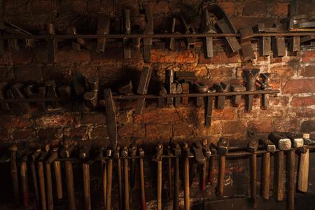 alte schmutzige Schmied Werkzeuge hängen und Verlegung