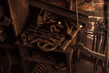 blacksmith: old dirty blacksmith tools hanging and laying