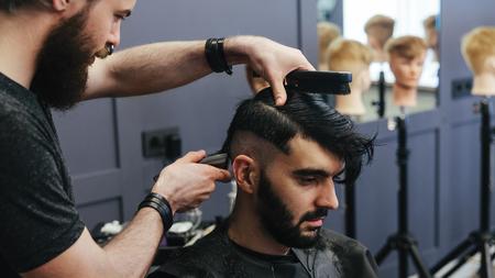 Homme peignage de coiffure et les cheveux de rasage d'un client de sexe masculin au salon de coiffure