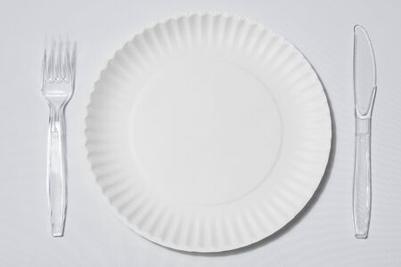 empty singleuse white paper plate with set of clear plastic fork and knife on white background or tablecloth 免版税图像