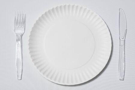 lege singleuse Witboek bord met set van doorzichtige plastic vork en mes op witte achtergrond of tafellaken