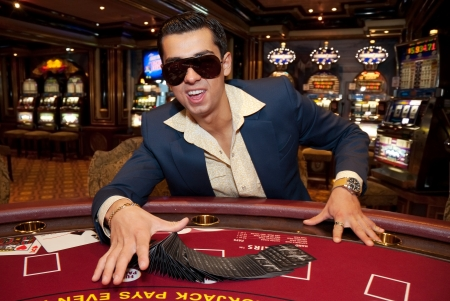 young man in trendy clothes  playing cards in casino photo