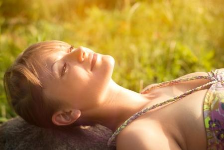 lying in grass: Hermosa mujer joven y sana acostado en la piedra
