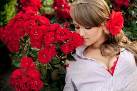 romantic young woman in flower garden smelling red roses photo