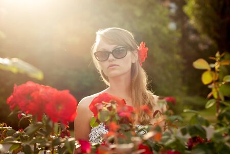 young sexy model in flower garden smelling red roses photo