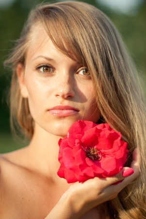 close-up portrait of young sexy girl with red flower photo