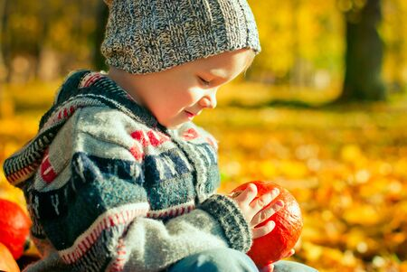 cute little boy playing with pumpkin in the park photo