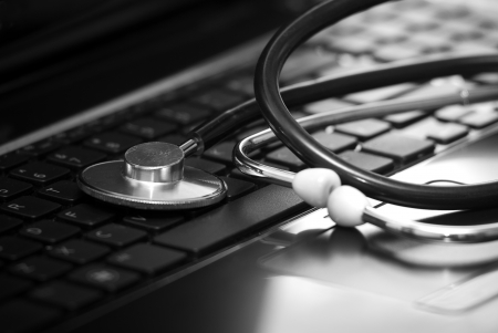 personal service: Silver stethoscope lying down on an laptop