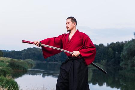 samurai sword: Man in ethnic samurai japanese clothing uniform with katana sword portrait