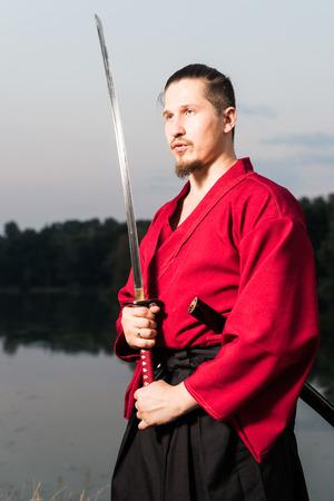 Man in ethnic samurai japanese clothing uniform with katana sword portrait
