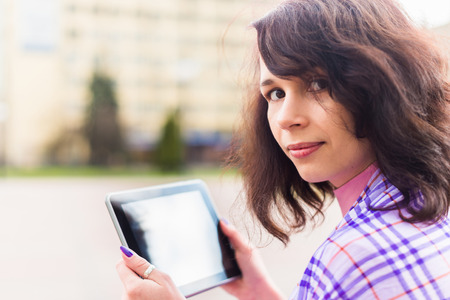 Young woman with Tablet reading from ebook photo