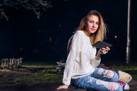 modern lifestyle: Young woman using tablet outdoor sitting on bench, smiling. Stock Photo