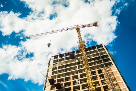 Tall building construction and crane under a blue sky with clouds